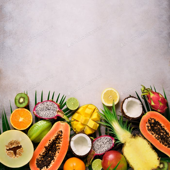 Exotic fruits and tropical palm leaves on grey concrete, background - papaya, mango, pineapple