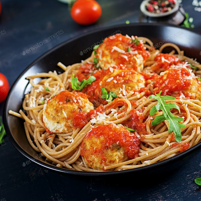 Spaghetti with meatballs and parmesan cheese in bowl on light rustic wood background.