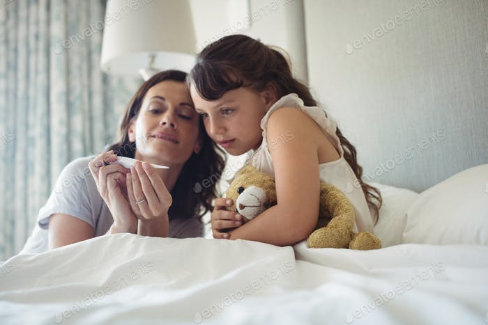 Mother showing temperature on thermometer to her daughter