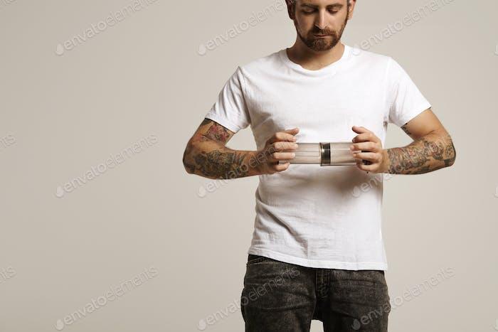 Hipster en camiseta blanca sosteniendo aeropress