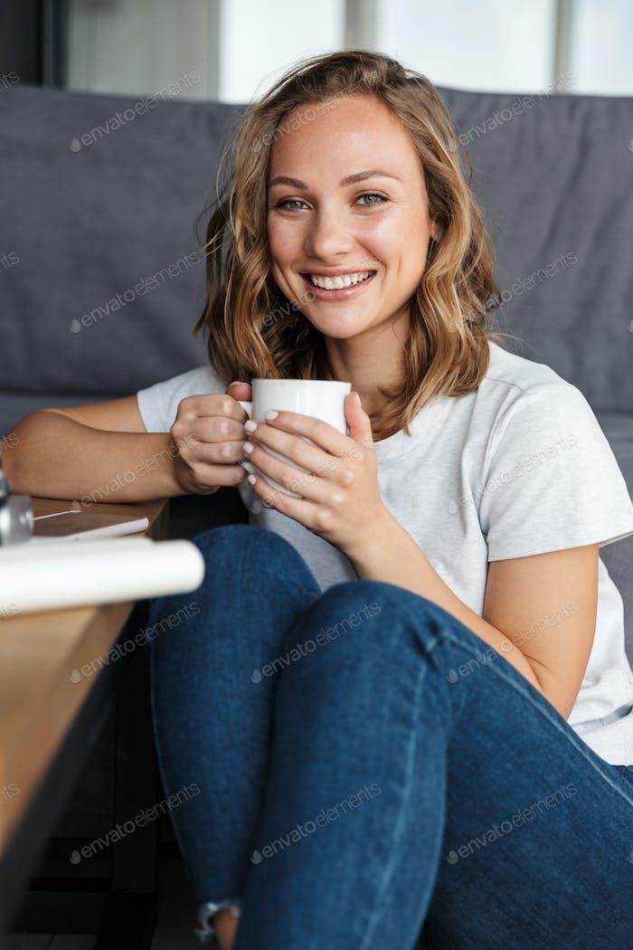 Образ счастливой привлекательной женщины, улыбающейся и пьющей кофе
