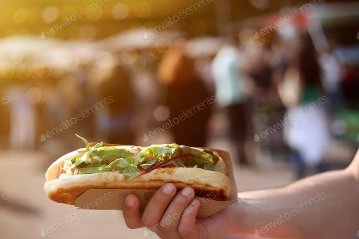 Nahaufnahme eines Hot Dog in der Hand gegen verschwommenes Streetfood-Festival im Sommer.