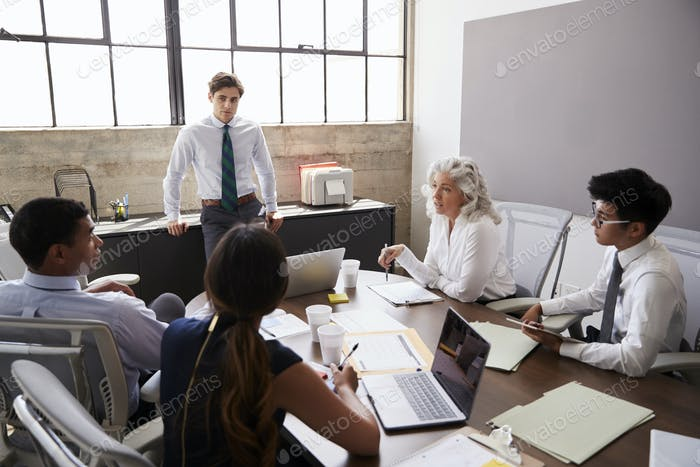 Young male manager stands listening to team at a meeting