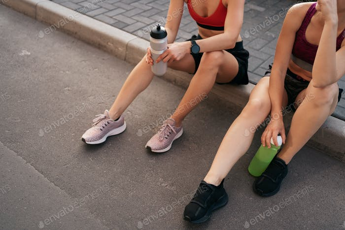 Portrait of two young beautiful sport woman resting after workout in the city