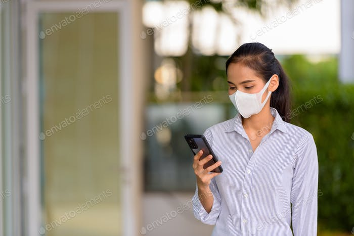 Happy woman wearing face mask to protect from coronavirus Covid-19 while using phone