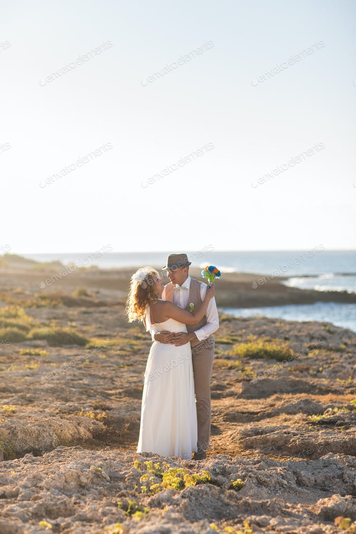 Bride and groom by the sea on their wedding day.