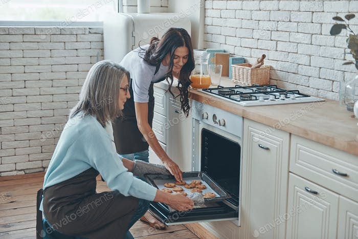 Beautiful young woman and her mother cooking together while spending time at the domestic kitchen