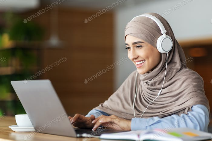 Cheerful muslim woman studying online, cafe interior