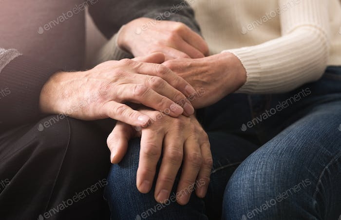 Together till end. Elderly couple holding hands