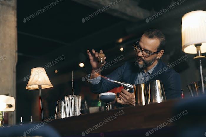 Barman is making cocktail at night club.