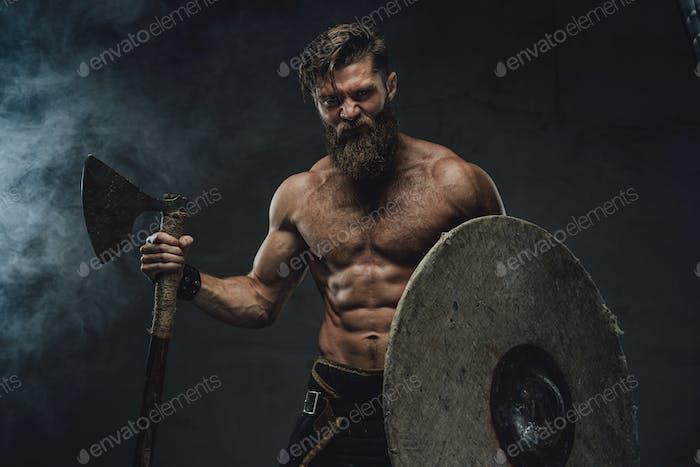 Mittelalterlicher Wikinger mit Axt und Helm in dunklem Hintergrund