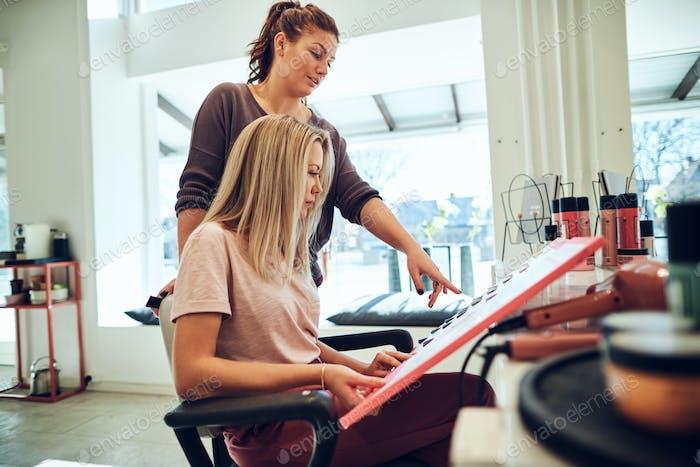 Young woman sitting in a salon chair choosing hair dye