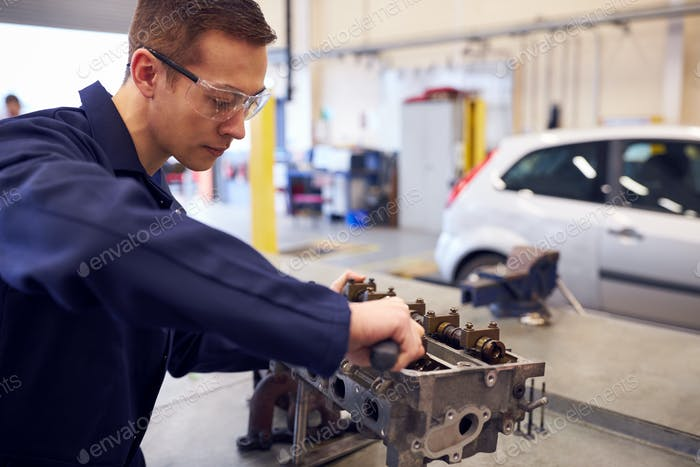 Female Student Works On Car Engine Block On Auto Mechanic Apprenticeship Course At College