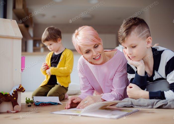 Eine junge Frau mit zwei Kindern, die Buch lesen und auf dem Boden spielen.