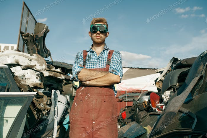 Dirty repairman in welding glasses on car junkyard