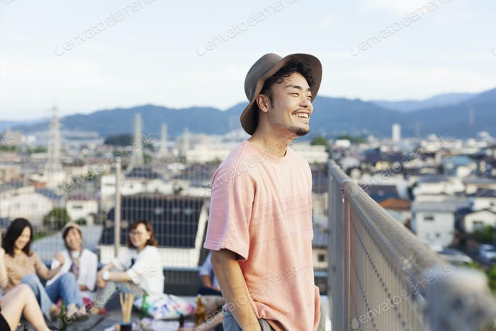 Smiling young Japanese man standing on a rooftop in an urban setting.