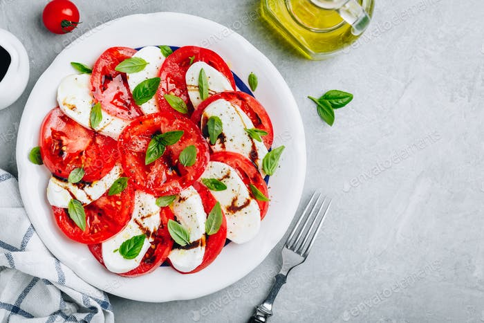 Tomaten, Basilikum, Mozzarella Caprese-Salat mit Balsamico-Essig und Olivenöl.