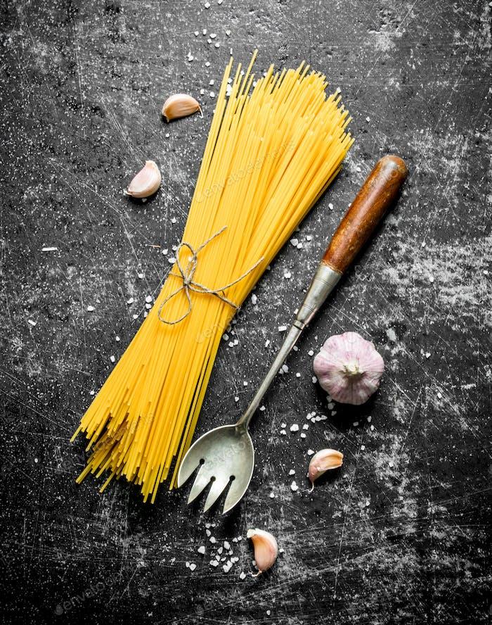 Rohe Spaghetti mit Knoblauch und einer Schöpfkelle.