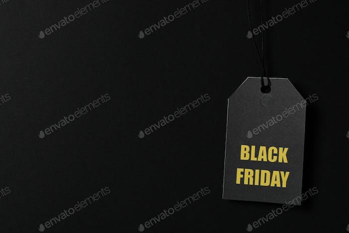 Inscription Black Friday on price tag on black background, copy space