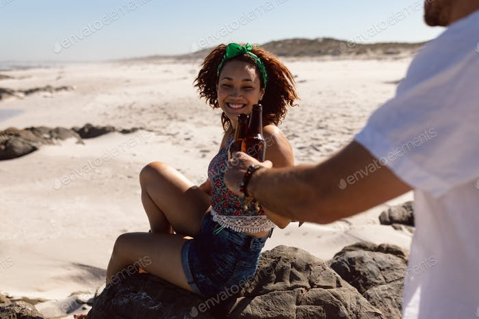 Rear view of happy young Mixed-race couple toasting beer bottle on beach in the sunshine