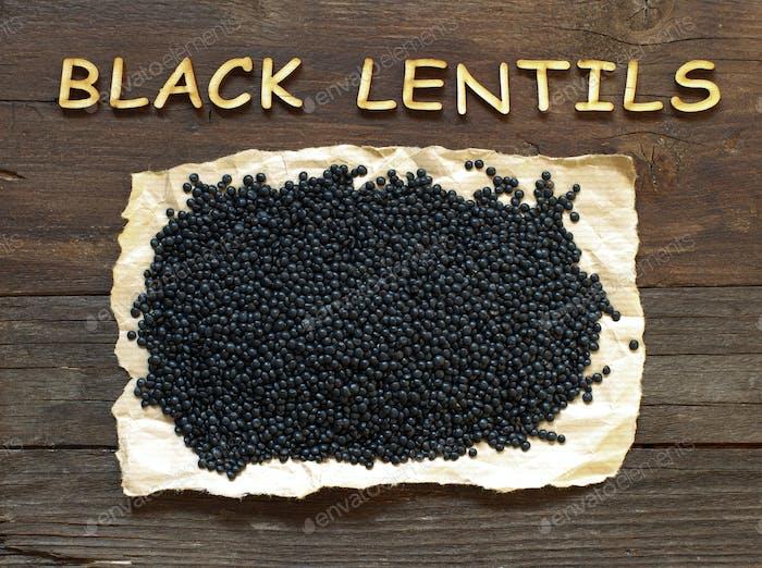 Haufen von schwarzen Linsen mit einem Holzwort