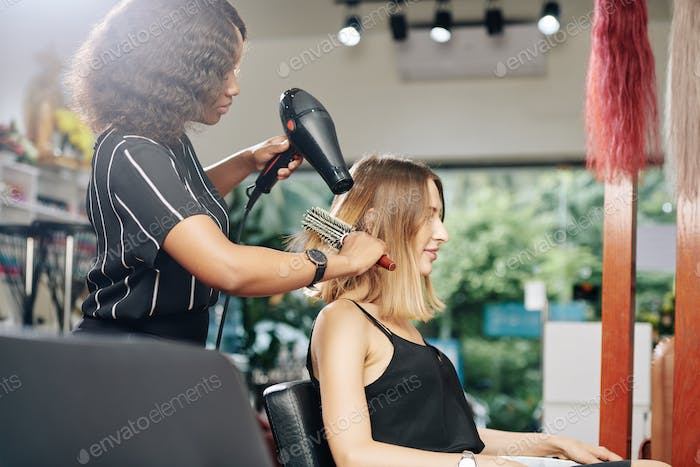 Young woman having her hair blowdried
