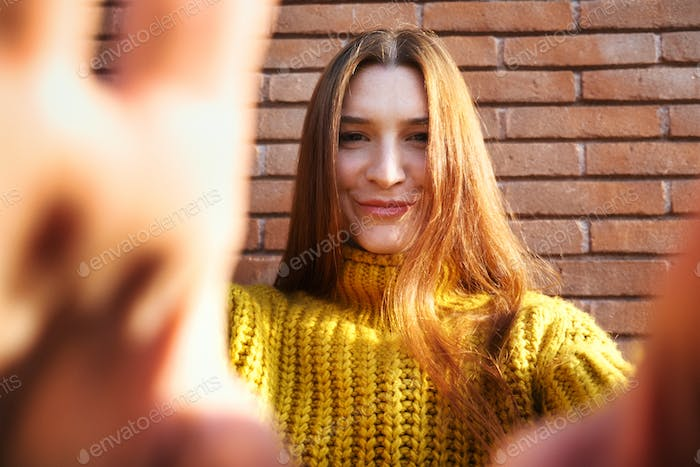 Young Redhead Woman Covering Camera Lens With Hands
