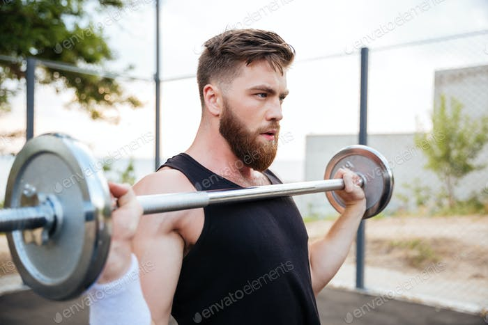 Serious young man athlete standing and holding barbell