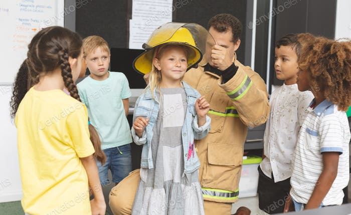 Caucasian firefighter teaching to schoolkids about fire safety in classroom