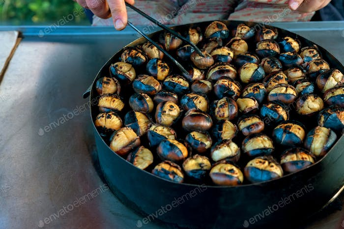 Chestnuts roasting, blacked and bursting open, from a street vendor in autumn.