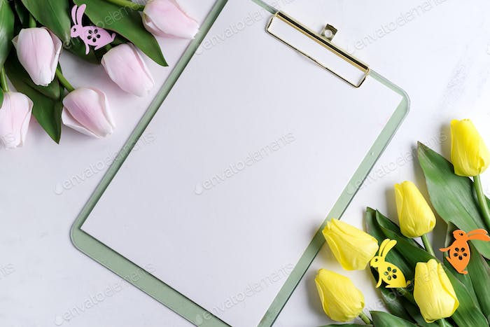 Clipboard with spring tulips with easter bunny on marble background with sample text