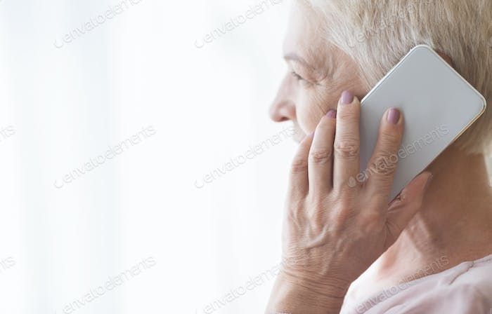 Close up of mature retired woman talking by smartphone