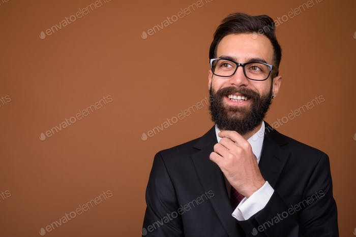 Young handsome bearded Persian businessman against brown backgro