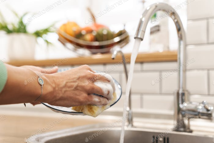 Woman indoors at home wash the dishes at the kitchen.