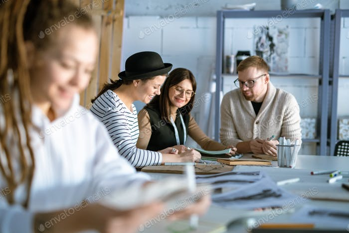 Group of happy young designers or students discussing creative ideas
