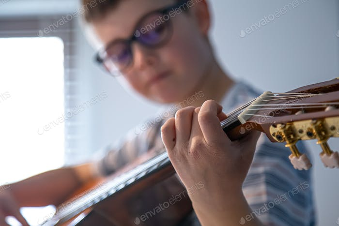 Close-up, hand of a boy playing a classical guitar.