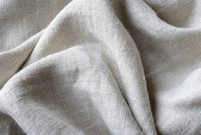 Gathered and folded texture of woven linen fabric
