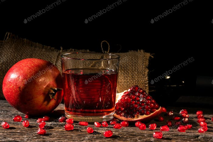 Pomegranate fruit, wine in glass and wine bottle