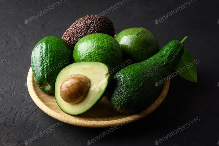 Fresh avocado fruit on a wooden plate