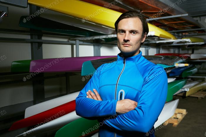 Portrait of professional Caucasian male canoeist standing against boats
