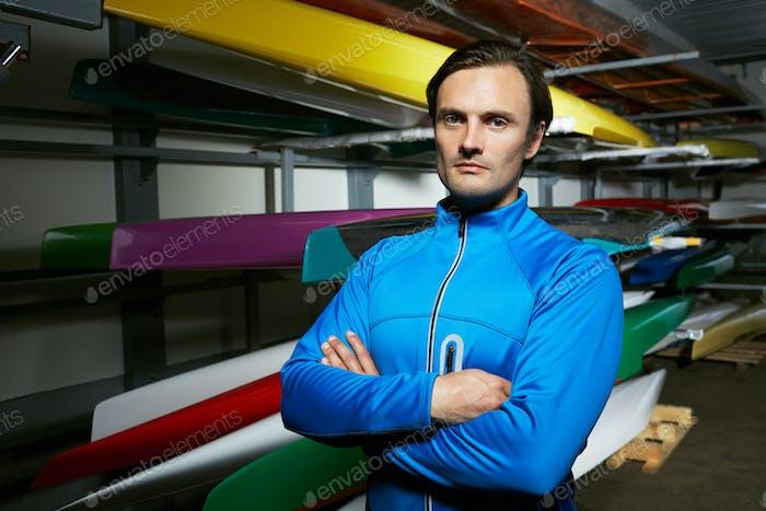 Retrato de canoist masculino profesional caucásico de pie contra los barcos