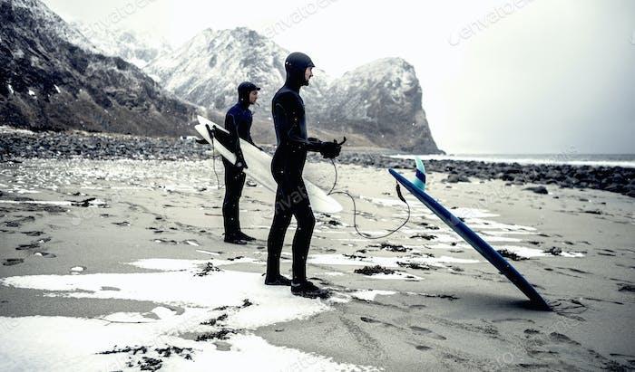 Zwei Surfer tragen Neoprenanzüge und tragen Surfbretter stehen an einem Strand mit Bergen dahinter.