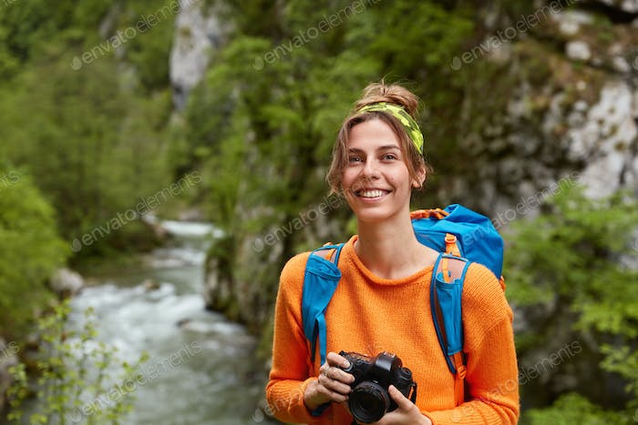 Positive backpacker covers distance, looks far away with glad dreamy expression, holds camera, makes