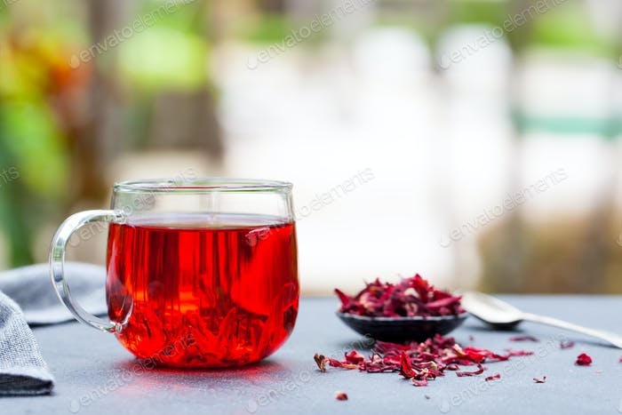 Hibiscus Tea in Glass Cup. Grey Background. Copy Space. Outdoor background.