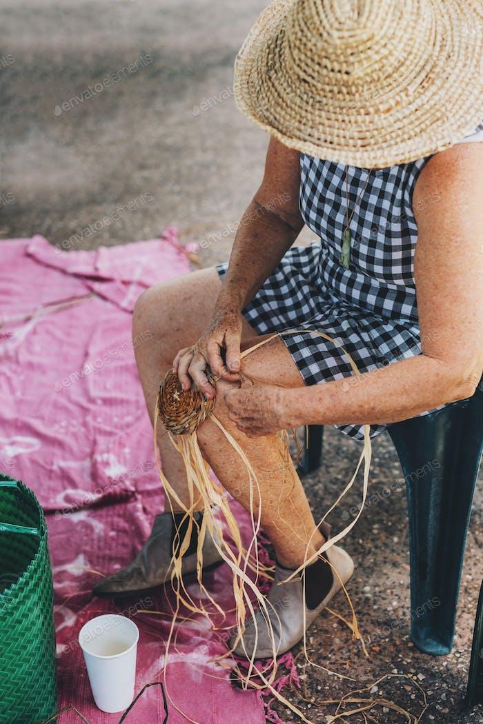 Old female weaving basket on the craft workshop. Hands holding the craftwork, close up shot