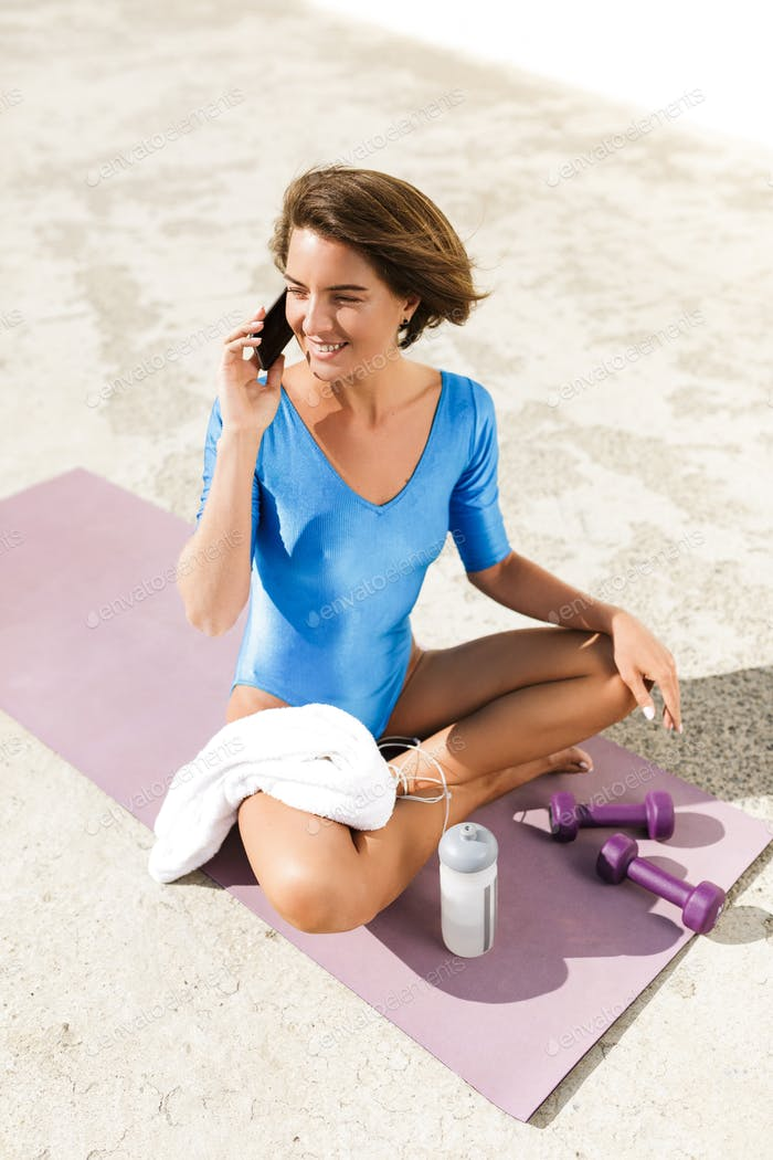Woman with dark short hair in blue swimsuit sitting on yoga mat and talking on her cellphone
