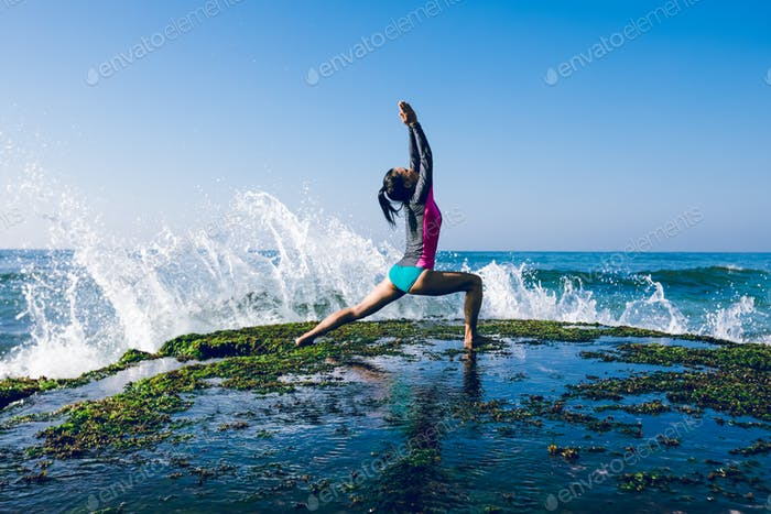 Woman practice yoga at seaside besides the giant sea waves