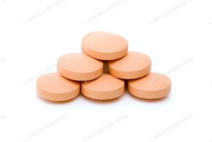 Few orange tablets lie in form of pyramid