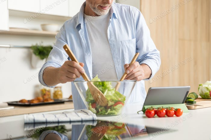 Cropped image of mature man cooking salad using tablet