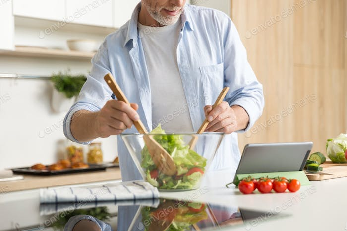 Thumbnail for Cropped image of mature man cooking salad using tablet